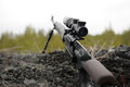 Sniper rifle with telescopic sight in the woods Royalty Free Stock Image