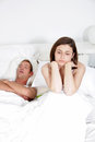 Snoring man distraught woman lying on his back in bed loudly while his wife unable to sleep sits up with a resigned angry Royalty Free Stock Photos