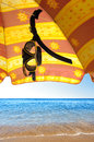 Snorkeling glasses hanging in a red and yellow sunshade in a beach by the seashore Royalty Free Stock Image