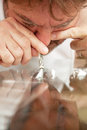 Snorting cocaine man off of his glass coffee table with a rolled up dollar bill Stock Image