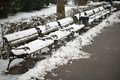 Snow on benches row of wooden in city park covered with Royalty Free Stock Photography