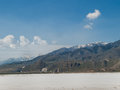 Snow capped mountains near salt flats white clouds in a blue sky highlight a clear day with in the distance and middle ground a in Royalty Free Stock Images