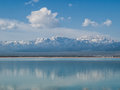 Snow capped mountains reflected in blue lake white clouds a clear sky and a a Royalty Free Stock Image