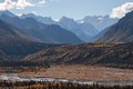 Snow capped peaks in fall rugged rise above autumn lowlands Royalty Free Stock Photo