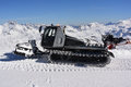 Snow cat grooming a slope in austria mountains in the background view from obertauern zehnerkarbahn top station Royalty Free Stock Photography