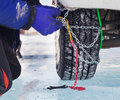 Snow chains man installing chain on car Royalty Free Stock Photo