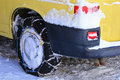 Snow chains tire chains attached to the drive wheels a yellow car with parking on snowy path during winter Stock Photography