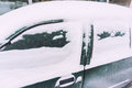 Snow covered car side of a in in a cold winter Stock Image