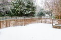 Snow covered deck on wood and fence with evergreens in background Royalty Free Stock Photos