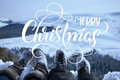 Snow-covered feet of two hikers on a winter landscape with text Merry Christmas. Calligraphy lettering Royalty Free Stock Photo