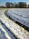 Snow-covered field with a small brook