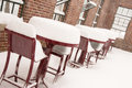 Snow covered furniture chairs and tables in an open outdoor patio area Stock Photos