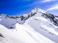 Snow covered high mountain peaks under cloudy panoramic skies in Europe. Great place for winter extreme sports. Royalty Free Stock Photo
