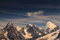 Snow covered mountains and rocky peaks in the french alps clouds Stock Image