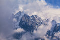Snow covered mountains and rocky peaks in the french alps clouds Royalty Free Stock Images