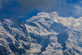 Snow covered mountains and rocky peaks in the french alps clouds Royalty Free Stock Photo