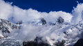 Snow covered mountains and rocky peaks in the french alps clouds Stock Photography