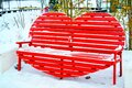 Snow-covered park bench in the shape of a heart Royalty Free Stock Photo