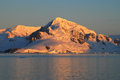 Snow covered peaks mountains illuminated by the setting sun in antarctica Stock Image