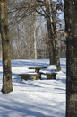 Snow covered picnic table a concrete in a park in winter Stock Image