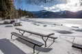 Snow covered picnic tables by frozen lake. Royalty Free Stock Photo