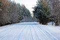 Snow-covered road in the forest Stock Photography