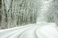 Snow covered road a winding on a tree lined street Stock Images