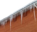 Snow-covered roof with icicles on white background Stock Photo