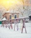 Snow-covered trees and swings in the city park Royalty Free Stock Photo