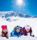 Snow day is happy day group of three kids years old boys and girls on in a row in mountains Royalty Free Stock Image