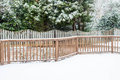 Snow on deck and evergreens wood fence with in background Stock Images