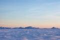 Snow desert and blue winter sky. Mountains on the horizon Royalty Free Stock Photo