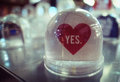 Snow globe with red heart and YES word with beautiful blurred bo Royalty Free Stock Photo
