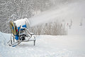 Snow gun (pulverizer) disperse artifitial snow on mountain, Stock Photo