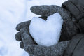 Snow heart in his hands of are holding close up Royalty Free Stock Images