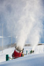 Snow-machine bursting artificial snow  over a skiing slope Royalty Free Stock Photo