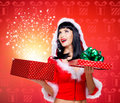 Snow maiden with a christmas gift with magic shining photo of surprised from box studio red background Stock Photography
