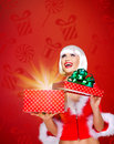 Snow maiden with a christmas gift with magic shining photo of surprised from box studio red background Royalty Free Stock Photo