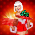Snow maiden with a christmas gift with magic shining photo of surprised from box studio red background Royalty Free Stock Photos