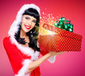 Snow maiden with a christmas gift with magic shining photo of surprised from box studio red background Stock Photos