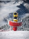 Snow maker modern cannon near the ski piste with cloudy mountain in the background Royalty Free Stock Photography