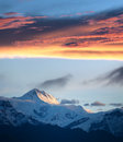 Snow mountain peak under burn clouds Stock Photo