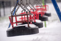 Snow in playground on swing seat a children s Royalty Free Stock Photography