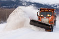 Snow plough clearing road in winter storm blizzard