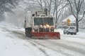 Snow plowing a sanitation vehicle is the road during the blizzard Stock Images