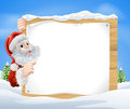 Snow scene christmas santa sign an illustration of a with claus peeking round the and pointing in the middle of a Stock Image