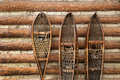 Snow shoes and a log cabin pair of vintage hanging on Royalty Free Stock Photos