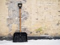 Snow shovel out in the snow standing against a worn brick wall Royalty Free Stock Photography