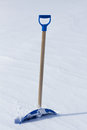 Snow shovel standing in the Royalty Free Stock Photos