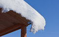 Snow slipping off roof slides the of a wooden house on a background of the cloudless sky Royalty Free Stock Photos